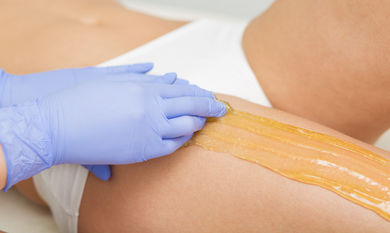 Beautiful woman having a sugaring depilation beauty treatment
